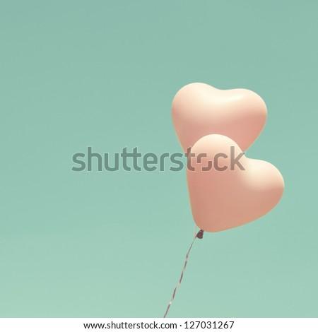 Love heart balloons on vintage sky