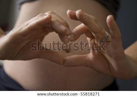 stock photo : love heart being made by a pregnant mother over her tummy with