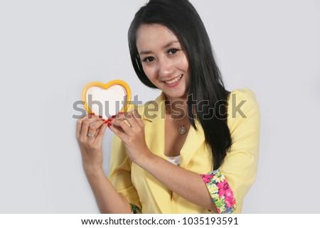 love heart in hand woman smilling. hands in shape of love heart. #1035193591