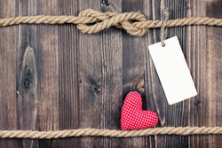 Love heart on vintage wooden planks with rope and paper tag background