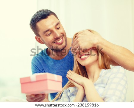 love, holiday, celebration and family concept - smiling man surprises his girlfriend with present at home #238159816