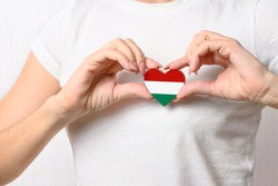Love Hungary. A girl holds a heart in the form of a flag of Hungary on her chest. Hungarian concept of patriotism