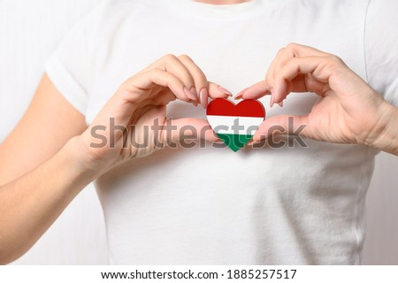 Love Hungary. A girl holds a heart in the form of a flag of Hungary on her chest. Hungarian concept of patriotism Сток-фото ©