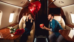 Love in the air. A beautiful couple is celebrating St Valentine's Day on a private jet. A man is giving a present in a red box to his girlfriend, who is sitting with her eyes closed.