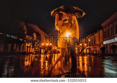 Love in the rain / Silhouette of kissing couple under umbrella