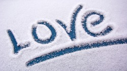 Love in the snow. The word love is drawn with your finger on the snow surface. Declaration of love. Sign of attention.