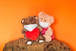 Love in times of COVID-19 quarantine. Cute teddy bears with big, red heart. Innocent children wearing a medical face masks.