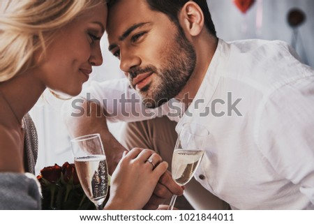 Love is in the air. Beautiful young couple drinking champagne and smiling while sitting face to face in the bedroom