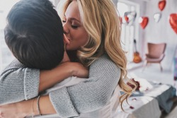Love is in the air. Beautiful young woman kissing her boyfriend while spending time in the bedroom