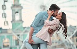 Love is in the air!Cute romantic couple spending time together in the city. Handsome bearded man and attractive young woman are in love. Hugging, kissing and having fun on the Ferris wheel background.