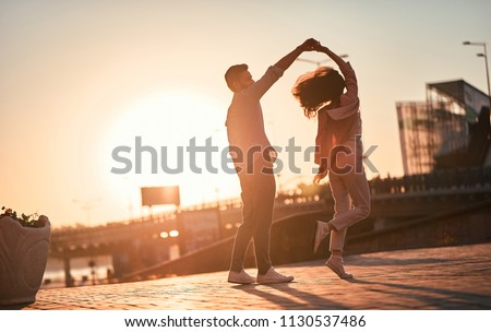 Love is in the air! Cute romantic couple spending time together in the city. Handsome bearded man and attractive young woman are in love. Dancing during sunset.