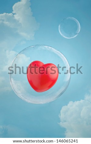 Love is in the air. Red heart floating in a soap bubble in the sky