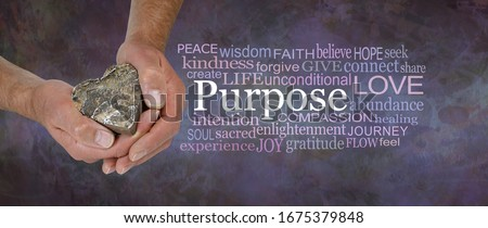 Love is our True Soul Purpose - male hands holding a wooden love heart beside a PURPOSE word cloud against a rustic dark purple brown stone grunge background                                 Stock photo ©