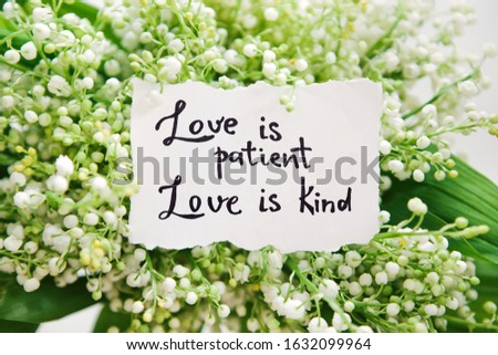 Love is patient, love is kind - calligraphy lettering on card in white flowers, biblical verce and religion concept Foto stock ©