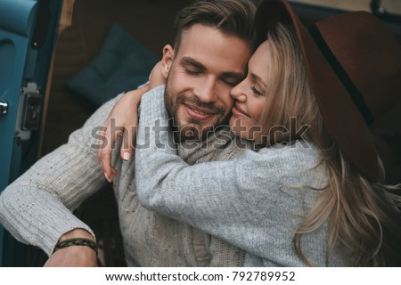 Love is the biggest treasure.  Beautiful young couple embracing and smiling while sitting in retro style mini van #792789952
