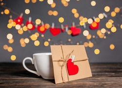 Love letter with a heart next to a cup on a background of lights, love and valentine concept on a wooden table