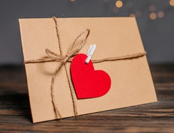 Love letter with a heart on a background of lights, love and valentine concept on a wooden table