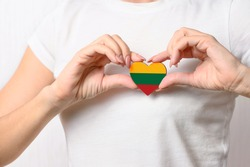 Love Lithuania. The girl holds a heart in the form of the flag of Lithuania on her chest. Lithuanian concept of patriotism