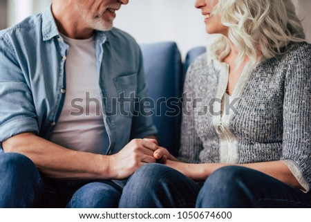 Love lives forever! Cropped image of senior couple at home. Handsome old man and attractive old woman are spending time together. Sitting on a sofa, hugging and holding hands.