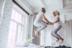 Love lives forever! Senior couple at home. Handsome old man and attractive old woman are enjoying spending time together. Having fun and jumping in bed.
