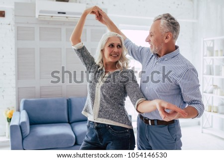 Love lives forever! Senior couple at home. Handsome old man and attractive old woman are enjoying spending time together while dancing.