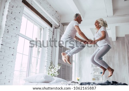 Love lives forever! Senior couple at home. Handsome old man and attractive old woman are enjoying spending time together. Having fun and jumping in bed. #1062165887