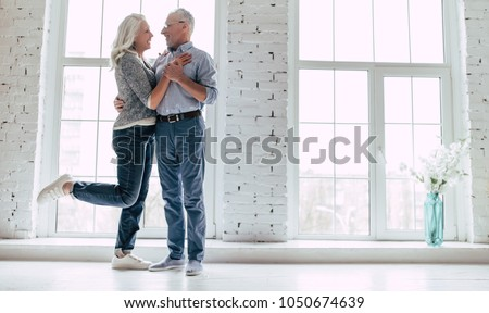 Love lives forever! Senior couple at home. Handsome old man and attractive old woman are hugging and enjoying spending time together.