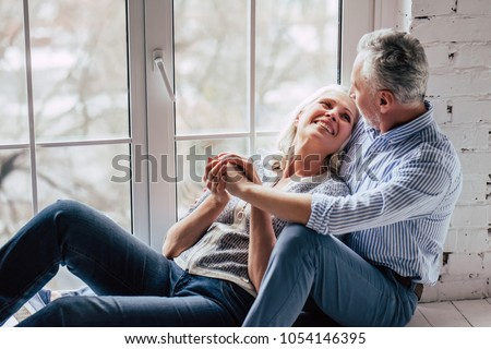 Love lives forever! Senior couple at home. Handsome old man and attractive old woman are hugging and enjoying spending time together while sitting on a window sill. #1054146395