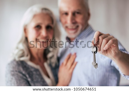 Love lives forever! Senior couple at home. Handsome old man and attractive old woman are spending time together while standing with keys in hands. Moving day