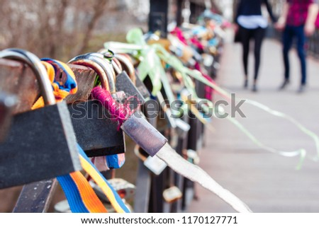 love locks with multi-colored ribbons attached to the bridge and a couple on the background as a symbol of love. This is to symbolically seal their eternal love\r