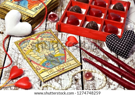 """Love magic ritual with red candles, tarot card Lovers, heart symbols and chocolate candies.  The English title on the card """"Lovers"""" means the word """"lovers"""".  Romantic vintage valentine's day concept"""