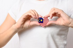 Love Malaysia. The girl holds a heart in the form of the flag of Malaysia on her chest. Malaysian patriotism concept