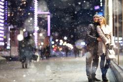 Love man and woman embracing outdoors winter snowfall