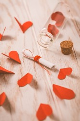 Love message in a bottle with paper hearts on wooden background -happy Valentine