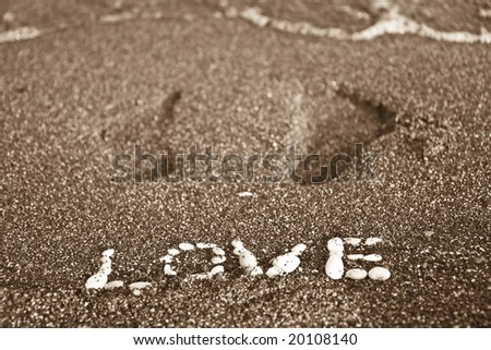 Love message written by white stones on a beach sand and footprints