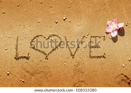love message written on the sand decorated with flower