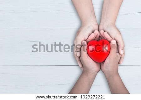 Love Mom Concept : Woman holds her young kids hands supporting red heart on brown wooden table background. Free space for text of Mother's Day celebration. #1029272221
