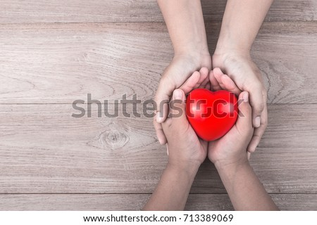 Love Mom Concept : Woman holds her young kids hands supporting red heart on brown wooden table background. Free space for text of Mother's Day celebration. #713389069
