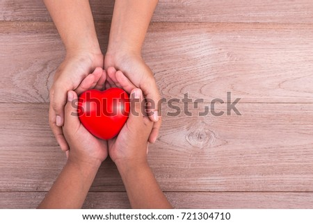 Love Mom Concept : Woman holds her young kids hands supporting red heart on brown wooden table background. Free space for text of Mother's Day celebration. #721304710
