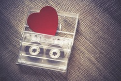 Love music concept. Valentines day background with audio tape cassette and a red heart. Cross processed image with shallow depth of field