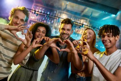 Love my friends, young men and women showing heart signs while posing together for camera, multiracial group of friends hanging out at party in the bar. Focus on hands.