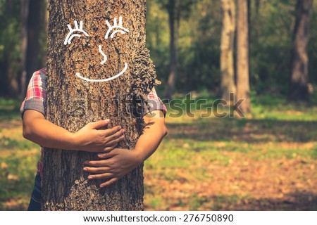 Love nature concept, woman give a hug behind tree trunk with drawing of tree's smile face