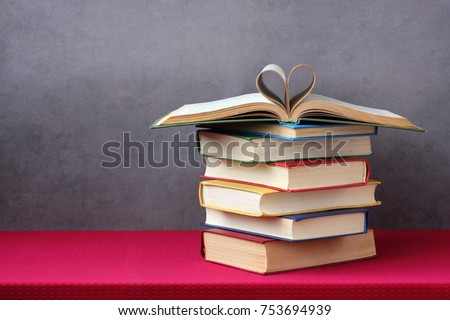 Love of books, reading. Stack of books in the colored cover lay on the table. Open book with curled leaves in the shape of a heart. Library, education.  Empty space for Your text on the left.