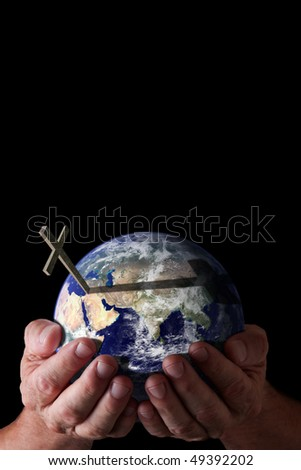 Love of God for world concept.  God's hands holding world with cross on isolated black background. Earth image courtesy of NASA.