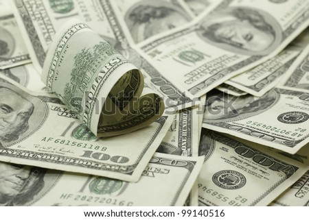 love of money heart shaped 100 dollar bill on pile of 100 dollar bills