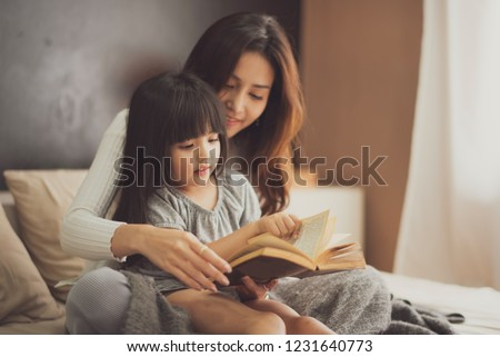Love of young mother and daughter. Teaching reading a book on the bed at home. mother and daughter look at the book feel good and happy