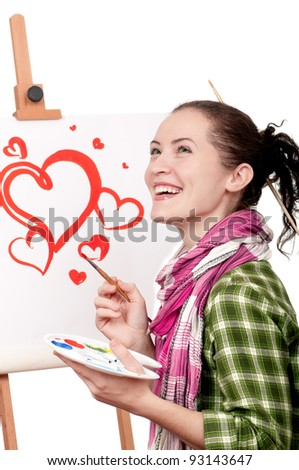 Love or Valentine day - concept image. Beautiful girl with brushes near easel, painting on canvas.