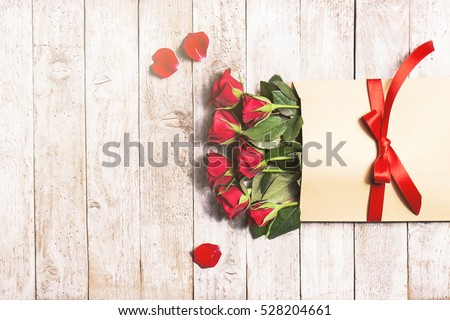 Love or valentine's day concept. Red beautiful roses in envelope with red ribbon on a wooden background. Top view #528204661