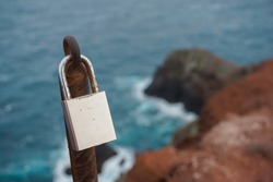 Love padlock locked to the remains of the fence on the cliff  and waves background.