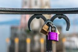 Love padlocks or love locks on a railing in the harbor of Lindau on blurred lighthouse background